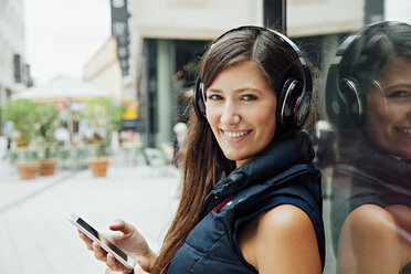 Portrait of smiling young woman with headphones and cell phone in the city - CHAF01915