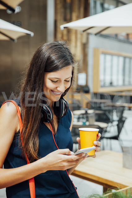 Smiling young woman with cell phone and takeaway drink in the city - CHAF01918
