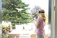 Woman wearing VR glasses navigating a drone - MAEF12281