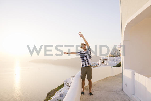 Greece, Santorini, Fira, happy man on holidays with hands up enjoying the sunset over the sea - GEMF01738