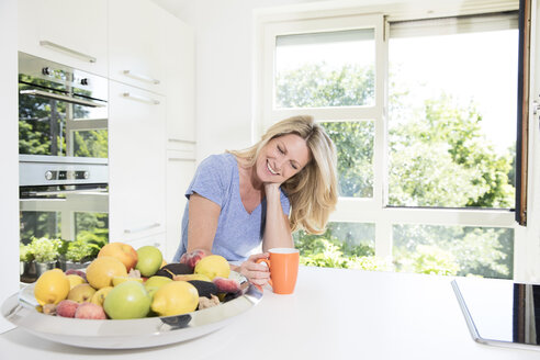 Portrait of smiling woman at home with cup of coffee and fruit bowl - MAEF12282