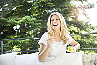 Happy woman on balcony with cup of coffee - MAEF12285