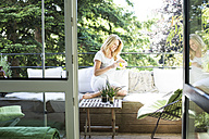 Woman relaxing on balcony with cup of coffee - MAEF12288
