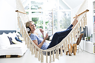 Relaxed woman at home lying in hammock listening to music - MAEF12294