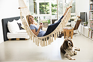 Relaxed woman with dog at home lying in hammock - MAEF12297