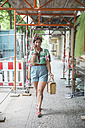 Woman walking and telephoning with smartphone under scaffolding - RTBF00984