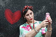 Woman taking a selfie next to heart painted on the wall - RTBF00987