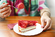 Close-up of woman eating strawberry cake in street cafe - RTBF00990