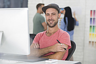 Office employee smiling at his desk - ZEF14066