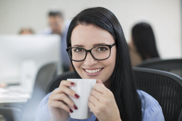 Employee enjoying a cup of coffee at her desk - ZEF14075