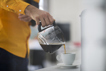 Employee with sling pouring coffee into cup at work - ZEF14081