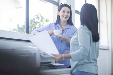 Employees chatting and laughing by photocopy machine - ZEF14108