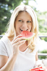 Mature woman sitting on balcony, eating water melon, portrait - MAEF12320