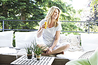 Mature woman sitting on balcony, drinking healthy smootis - MAEF12323