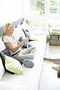 Mature woman sitting in living room, knitting - MAEF12329