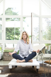 Blond woman sitting on coffee table, meditating - MAEF12338