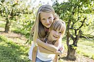 Two sisters having fun in garden - SHKF00760