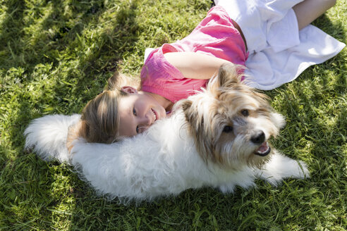 Girl lying with dog on meadow - SHKF00766
