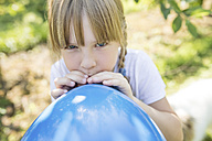 Girl inflating balloon outdoors - SHKF00772