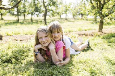 Two smiling sisters lying on meadow - SHKF00775