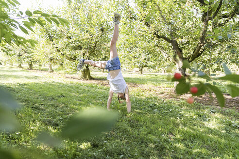 Girl doing a cartwheel on meadow - SHKF00781