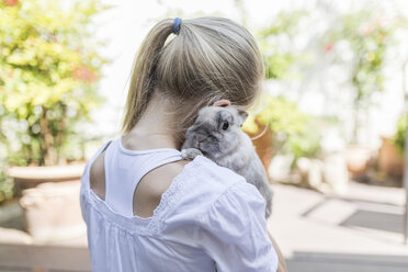 Girl cuddling with rabbit outdoors - SHKF00784