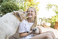 Happy girl with rabbit and dog outdoors - SHKF00787