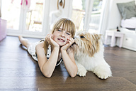 Girl with dog lying on the floor at home - SHKF00790