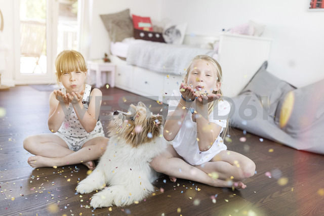 Two sisters with dog at home blowing confetti - SHKF00793