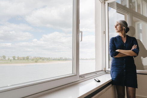 Businesswoman looking out of window in waterfront office - KNSF01759