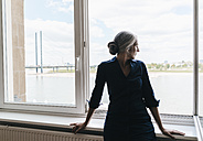 Businesswoman looking out of window in waterfront office - KNSF01762