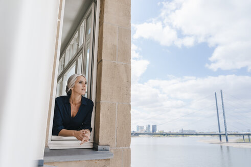 Businesswoman looking out of window in waterfront office - KNSF01765