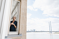 Businesswoman looking out of window in waterfront office - KNSF01768