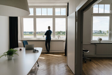 Businesswoman standing in modern office looking out of window - KNSF01777