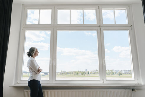 Businesswoman in office looking out of window - KNSF01780