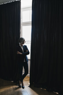 Businesswoman at curtain looking out of window - KNSF01783