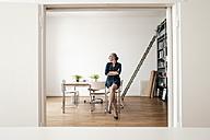 Businesswoman sitting in modern office - KNSF01789