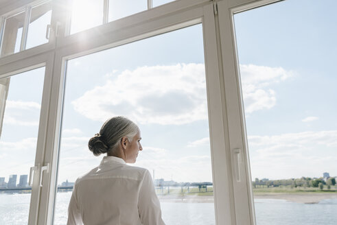 Businesswoman looking out of window - KNSF01792