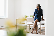 Businesswoman sitting on table in modern office - KNSF01810