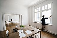 Businesswoman in office looking out of window - KNSF01816