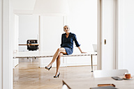 Smiling businesswoman sitting on table in modern office - KNSF01819