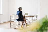 Businesswoman working on laptop in office - KNSF01822