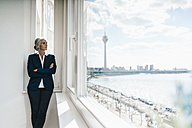 Businesswoman looking out of window in waterfront office - KNSF01828