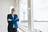 Portrait of confident businesswoman at the window in waterfront office - KNSF01831
