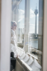 Businesswoman looking out of window - KNSF01840