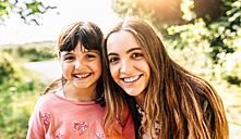 Portrait of two smiling girls outdoors - MGOF03429