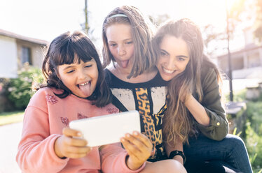 Three playful girls taking a selfie outdoors - MGOF03438