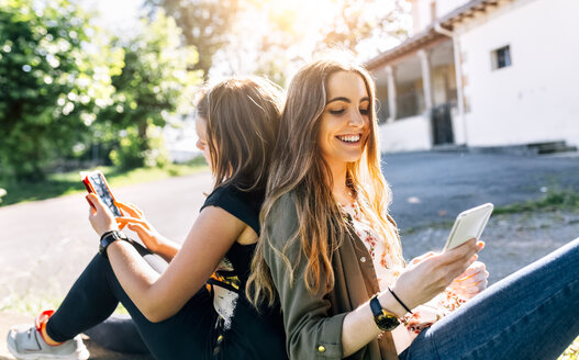 Two happy girls using their smartphones outdoors - MGOF03441