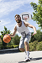 Man playing basketball on outdoor court - MAEF12344