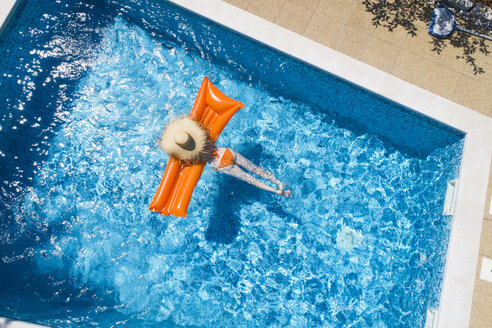 Back view of woman relaxing on orange airbed in swimming pool - MAEF12347